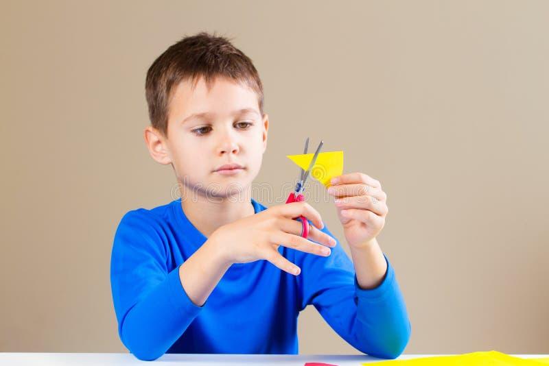Бумага вырезывания мальчика покрашенная с ножницами стоковое изображение