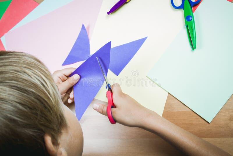 Бумага вырезывания мальчика покрашенная с ножницами на таблице стоковые изображения