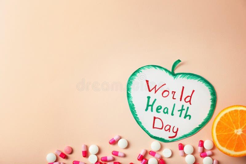 Бумага в форме яблока с днем здоровья мира фразы и таблеток на предпосылке цвета стоковая фотография