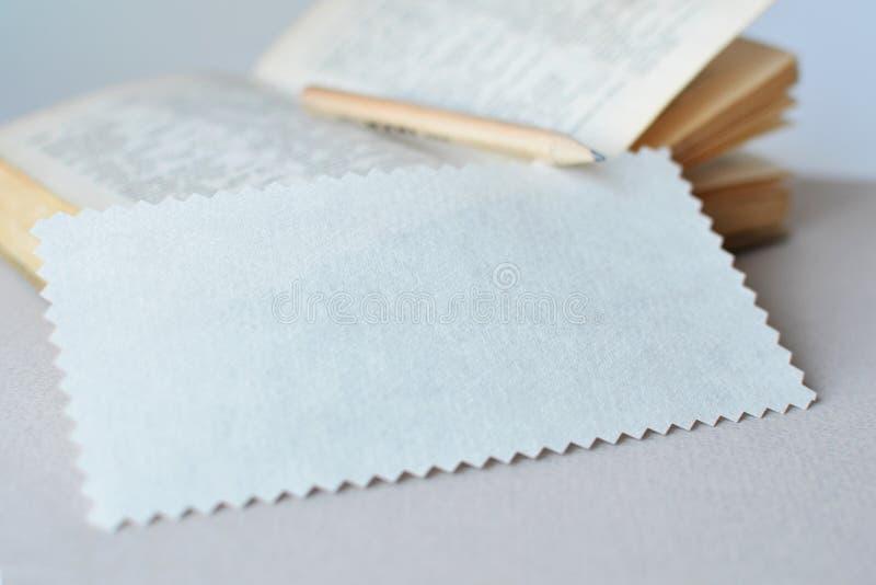 Бумага зигзага промокашки для примечаний на предпосылке книги и карандаша стоковые изображения