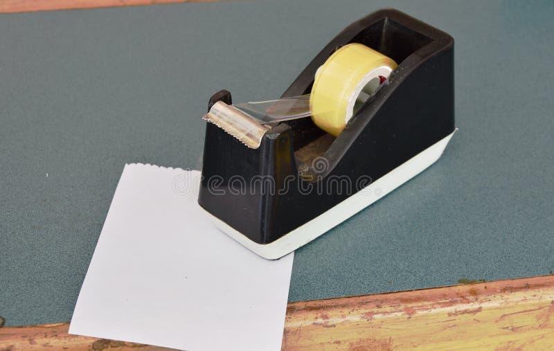 Бумага и чернота связывают распределитель тесьмой на встречном кассире в магазине стоковые фото