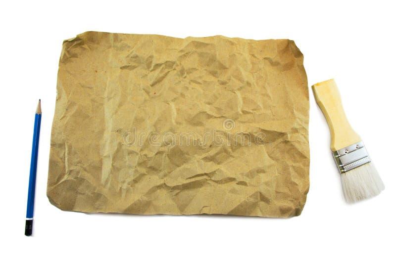 Бумага и paintbrush карандаша коричневая стоковые изображения