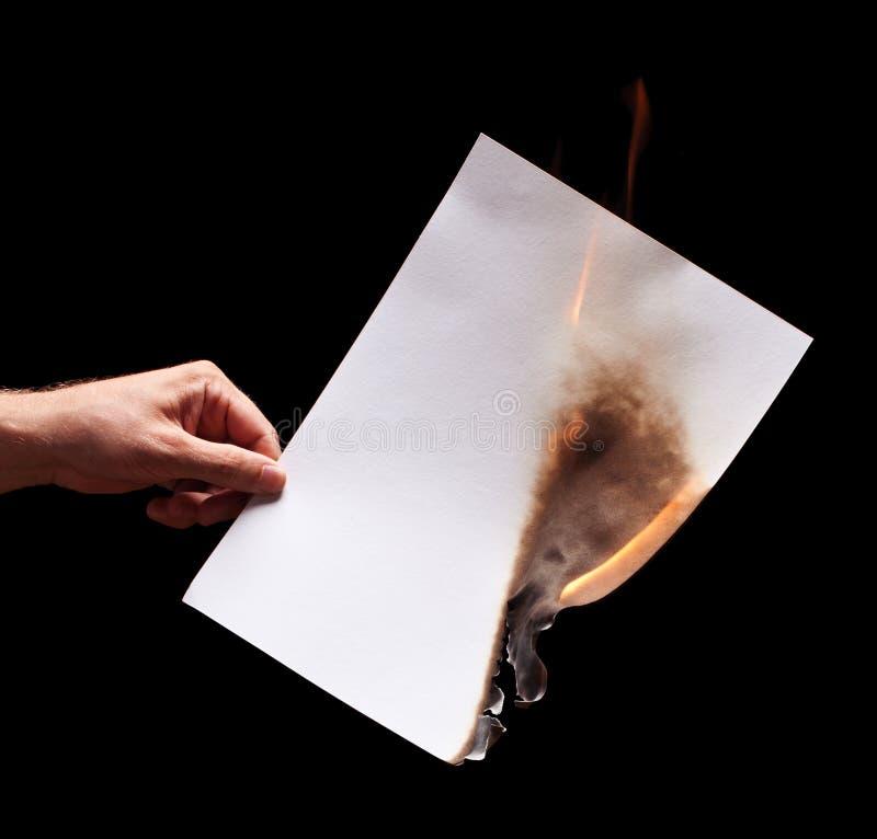 Бумага руки человека сгорели удерживанием, который стоковая фотография