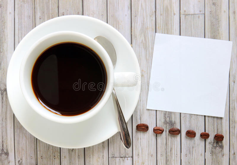 Бумага с горячими кофейной чашкой и кофейными зернами стоковое фото