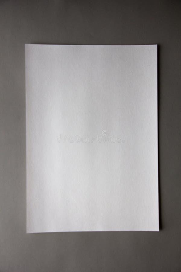 Бумага Unfocus вертикальная белая винтажная на серой предпосылке стоковое фото rf