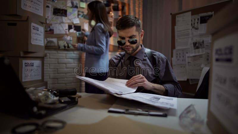 Бумаги чтения частного детектива уголовного дела, систематизируя информацию стоковое изображение
