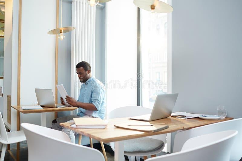 Бумаги чтения чернокожего человека в офисе стоковое фото
