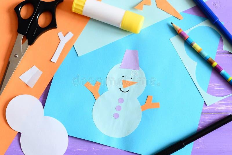 Бумажная карточка с applique снеговика и текст i любят зиму Ножницы, ручка клея, карандаш, отметки, бумажные листы и утили стоковая фотография