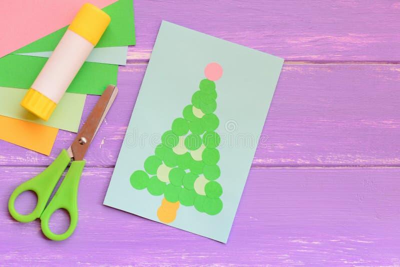 Бумажная поздравительная открытка рождества, листы покрашенной бумаги установила, ножницы, ручка клея на деревянном столе Легкие  стоковые изображения