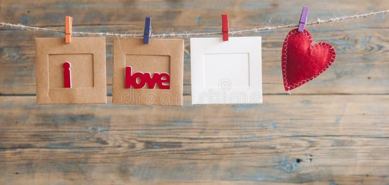 Бумажная рамка фото с написанным сообщением говоря по буквам я тебя люблю и r стоковое фото rf