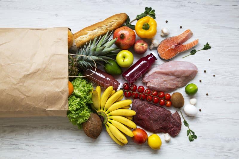 Бумажная сумка здоровых продуктов на белой деревянной предпосылке, взгляд сверху белизна студии макроса здоровья еды хлопьев мозо стоковые изображения
