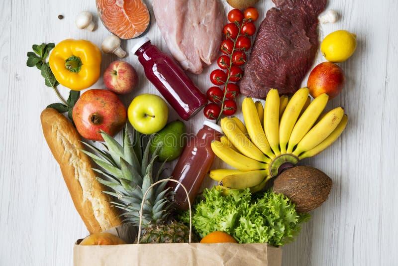 Бумажная сумка различных здоровых продуктов на белой деревянной предпосылке, крупном плане белизна студии макроса здоровья еды хл стоковая фотография
