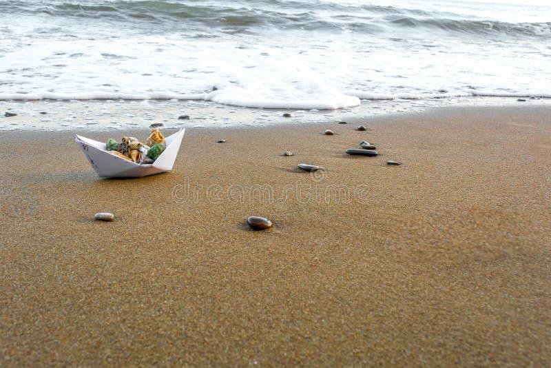 Бумажная шлюпка на пляже 4 стоковая фотография rf