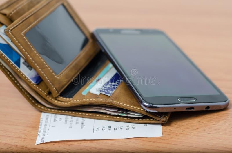 Бумажник, выскальзывание и умный телефон стоковое фото