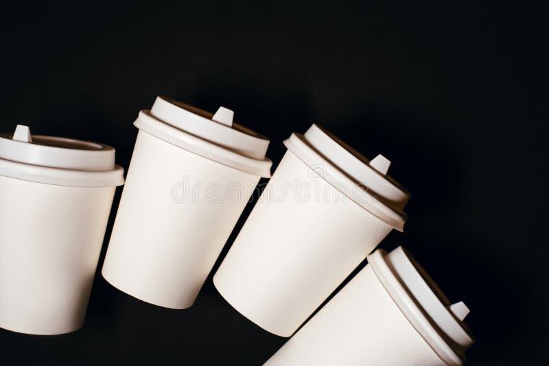 4 бумажного стаканчика на черной предпосылке стоковые изображения rf
