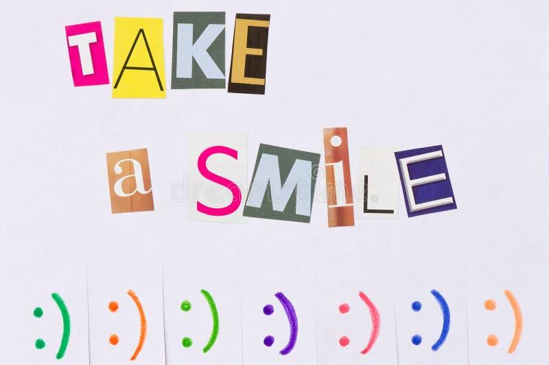 Бумажное объявление с фразой: Примите улыбку и с знаками улыбки стоковое изображение