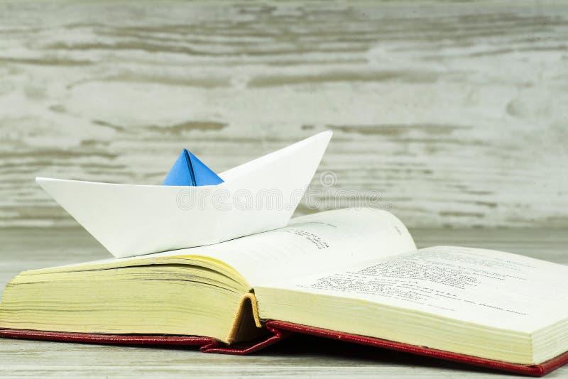 Бумажное плавание корабля через открытую книгу стоковые фото