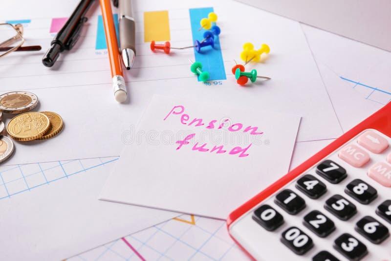 Бумажное примечание с ПЕНСИОННЫМ ФОНДОМ текста, калькулятором стоковые фотографии rf