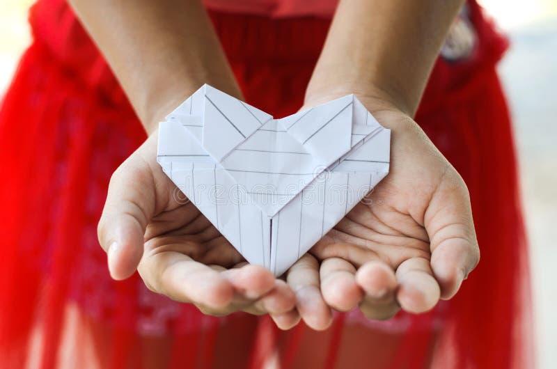 Бумажное сердце на руке маленькой девочки стоковые фотографии rf