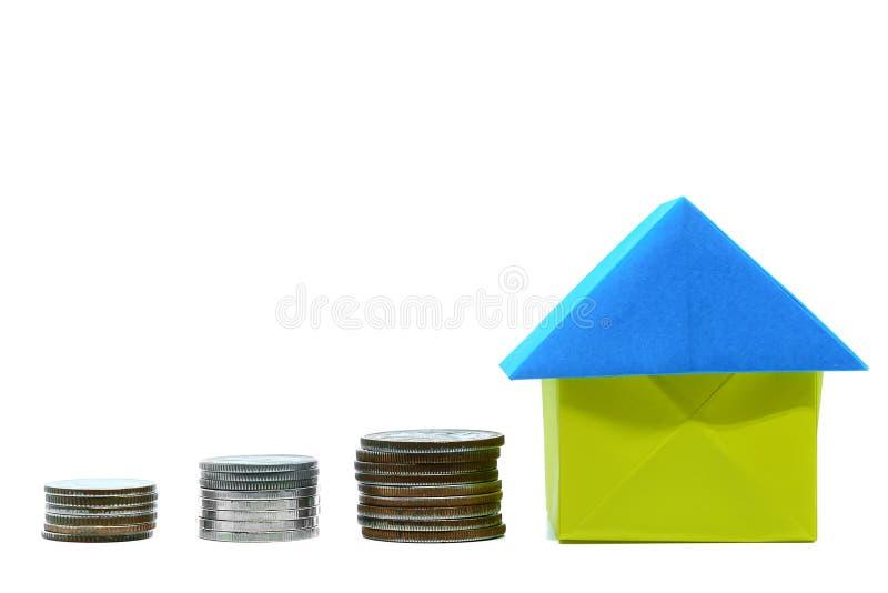 Бумажное origami дома с монеткой денег на белой предпосылке с космосом экземпляра стоковая фотография