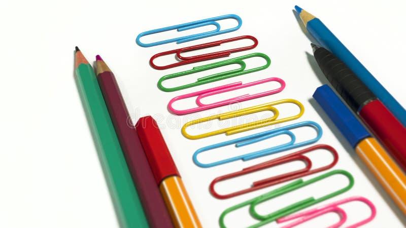 Бумажные зажимы, покрашенные карандаши и ручки помещенные в последовательности стоковое фото