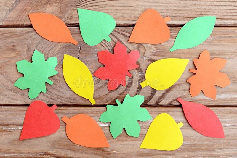 Бумажные листья осени сформировали и уравновесили с ножницами Простая форма домодельного оформления Дизайн много листьев покрашен стоковые фото