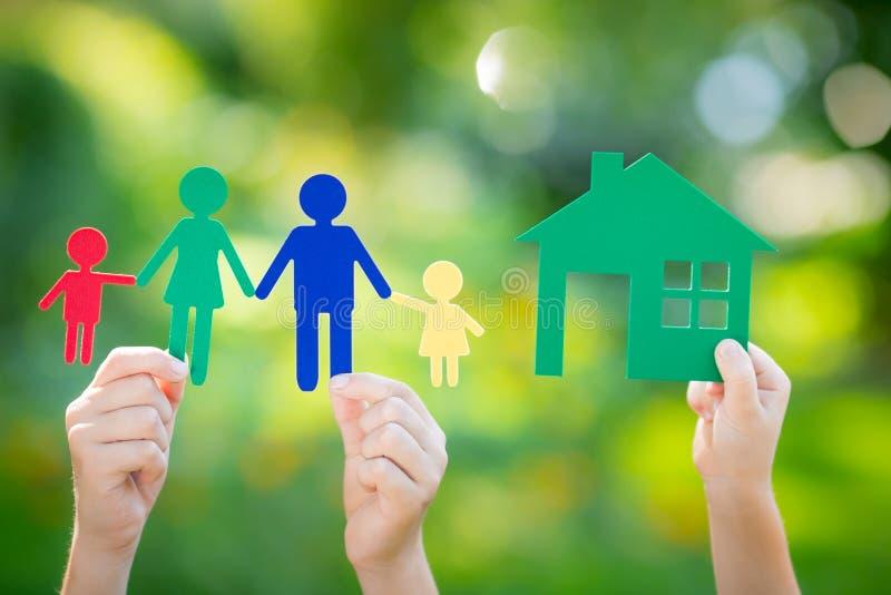 Бумажные дом и семья в руке стоковая фотография