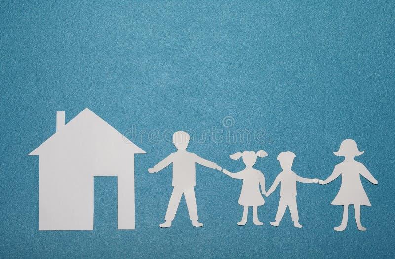Бумажные семья и дом на голубой текстурированной предпосылке Семья и домашняя принципиальная схема все типы страхсбора принципиал стоковая фотография rf