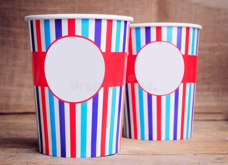 Бумажные стаканчики на деревянной поверхности Скопируйте космос на чашках стоковое фото rf