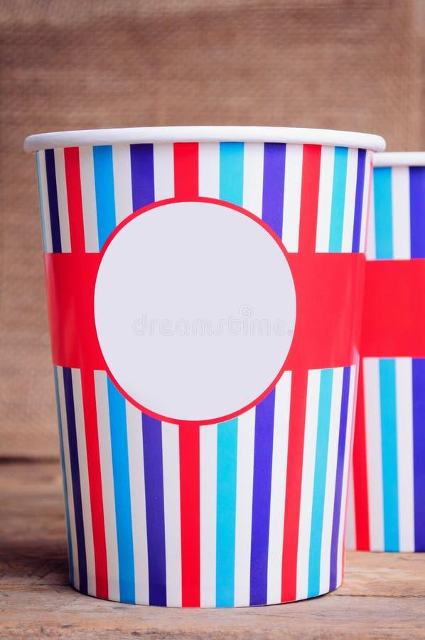 Бумажные стаканчики на деревянной поверхности Скопируйте космос на чашках стоковая фотография