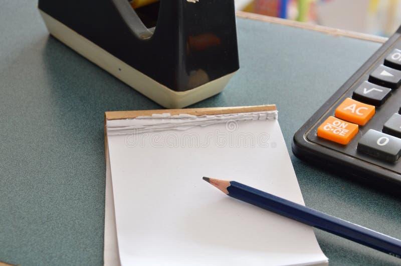 Бумажные тетрадь и карандаш на таблице стоковое изображение rf