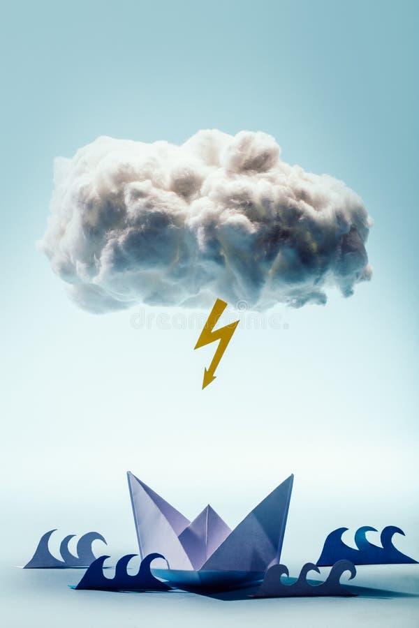 Бумажные шлюпка и волны под облаком и болтом стоковые изображения
