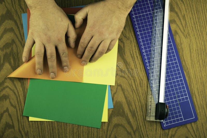 Бумажный зайчик для пасхи, рук делает origami из покрашенной бумаги, урок origami стоковое изображение