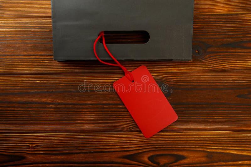 Бумажный мешок на деревянной предпосылке с биркой продажи Модель-макет для дизайна стоковое изображение