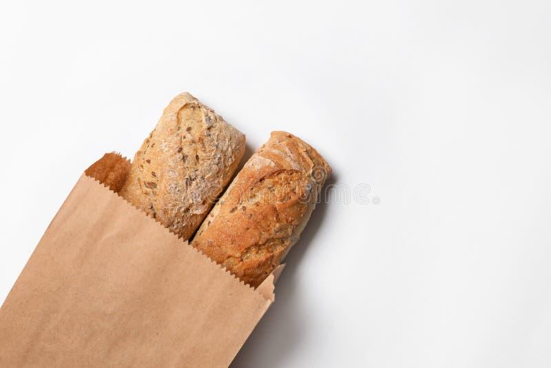 Бумажный мешок с хлебцами хлеба на белой предпосылке, взгляде сверху стоковые изображения