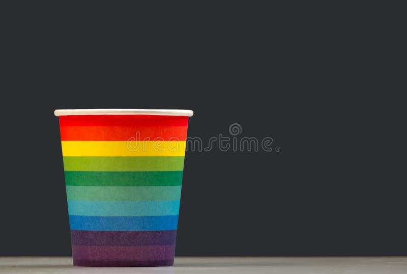Бумажный стаканчик покрасил как радуга на белой таблице, серой предпосылке Крася концепция символа LGBT или праздничный напиток в стоковое изображение