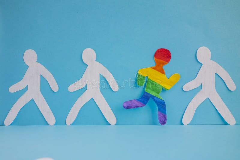Бумажный человек покрашенный в цветах флага LGBT бежит из серой массы стоковая фотография rf