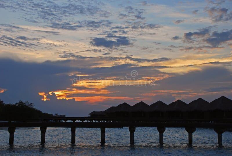 Бунгало Overwater в курорте во время захода солнца стоковое фото