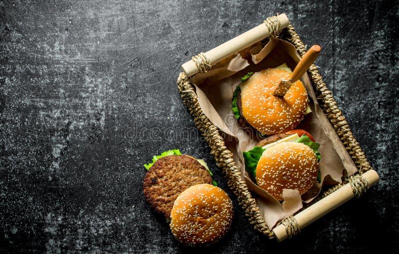 Бургеры в корзине с ножом стоковые фото