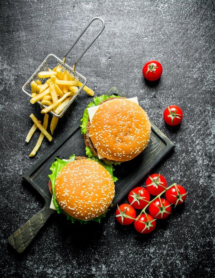 Бургеры с картофелем фри и томатами стоковая фотография