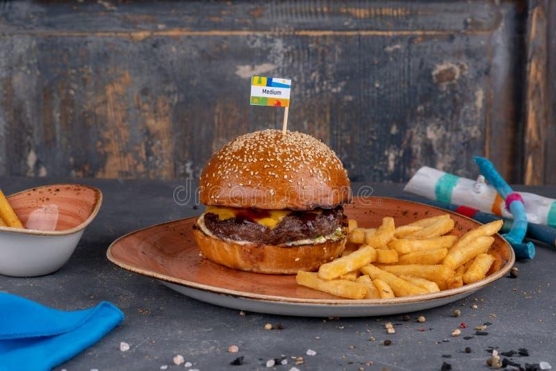 Бургер говядины ремесла с плюшкой сезама и французским картофелем фри на каменной предпосылке стоковая фотография