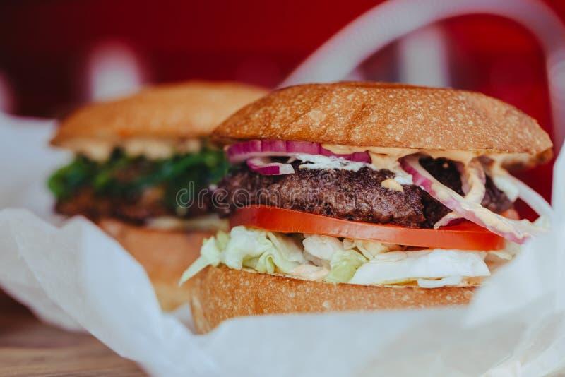 Бургер 2 классик роскошный утвержденный с сыром, с салатом, луками, томатами и плюшкой на деревянной предпосылке стоковое фото rf