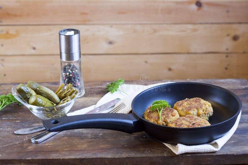 Бургер (котлета) в сковороде Бургер (котлета) в сковороде на деревянном столе стоковые изображения