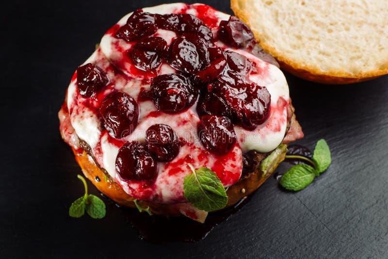 Бургер, сандвич гамбургера с котлетой семенить мяса, бри сыра, камамбера, вишни ягоды стоковая фотография