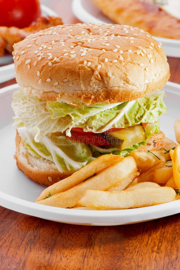 Бургер с овощами и зажаренными картошками на белом конце-вверх плиты стоковое фото