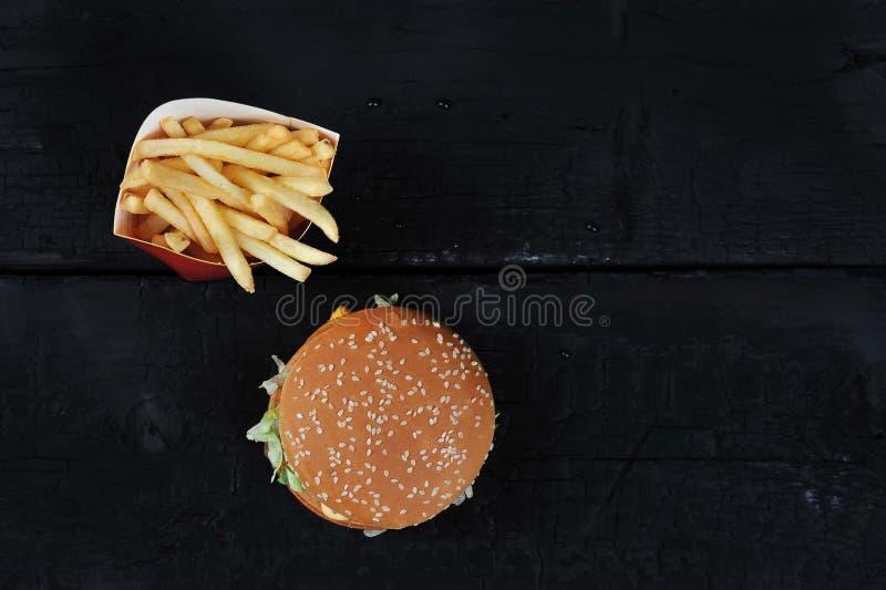 Бургер с плюшкой сезама и фраями француза стоковые изображения