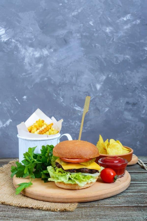 Бургер, французские фраи, обломоки, соус на деревянной предпосылке Еда улицы стоковая фотография rf
