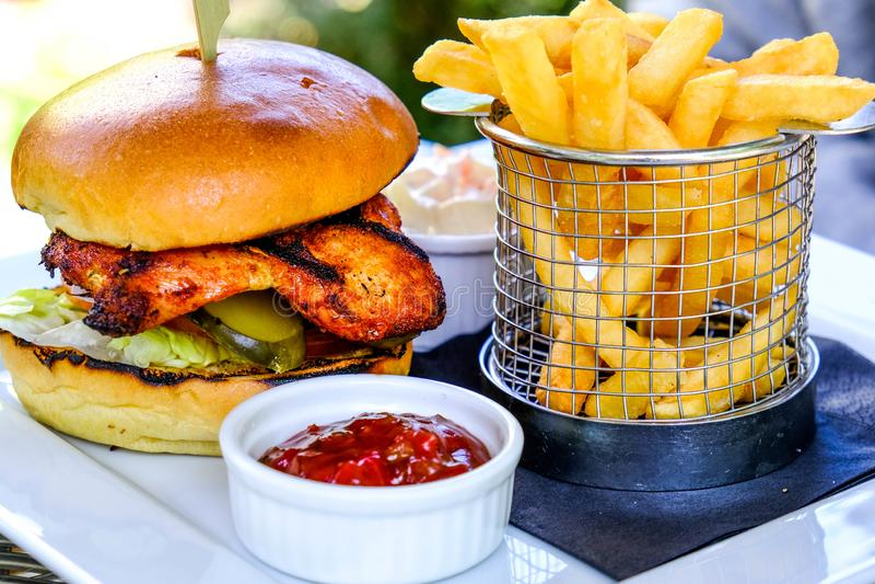 Бургер цыпленка Cajun с обломоками французского картофеля фри стоковая фотография rf