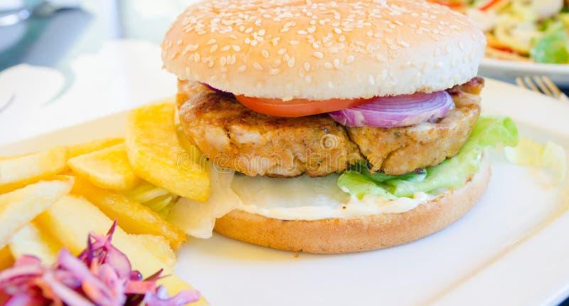 Бургер цыпленка с фраями и салатом и очень вкусным взглядом стоковая фотография