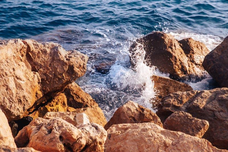 Бурное море с волнами и брызгает перерывы на острых камнях, теплый день, свет солнца стоковое фото rf